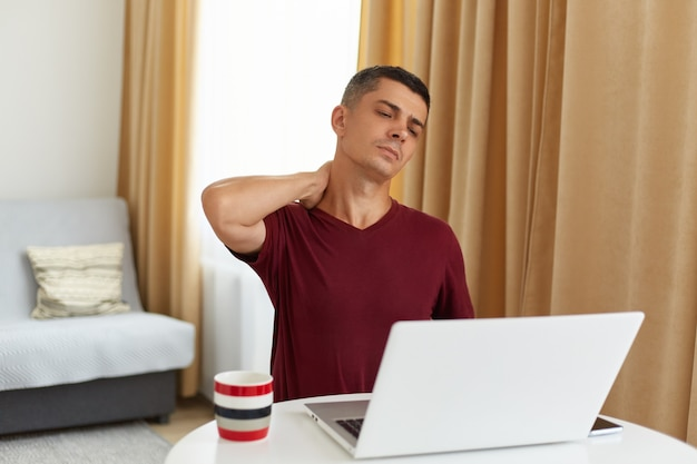 Indoor shot of tired man working online at home, sitting at table in living room against sofa, having lots freelance work, having pain in neck, massaging, looking at laptop display.