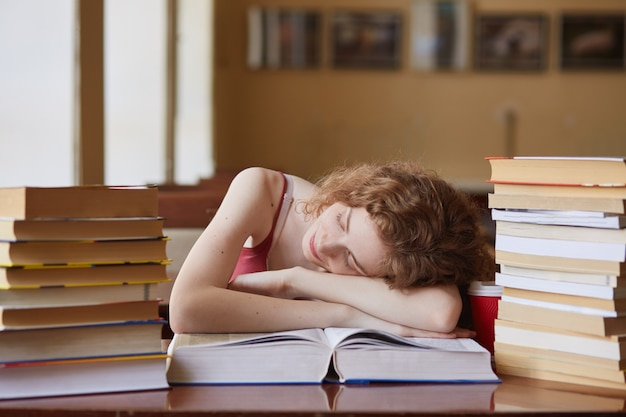 Indoor shot of tired student sleeping on book in reding room, being exhausted of studying, falling asleep while reading tutorial material for classes. education, knowladge and exams concept.