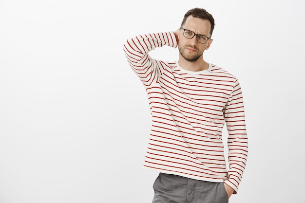 Indoor shot of troubled tired businessman in striped clothes, scratching back of neck