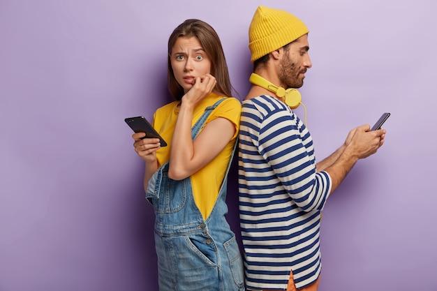 Tiro al coperto di due amici che si guardano l'un l'altro, usano gadget moderni