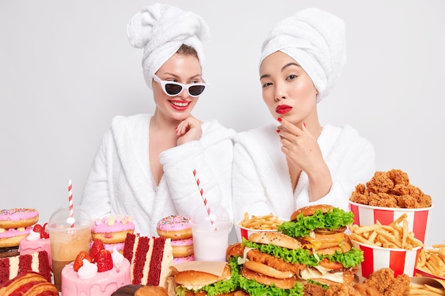 Indoor shot of two mixed race women lead unhealthy lifestyle eat junk food have harmful snack during meal time