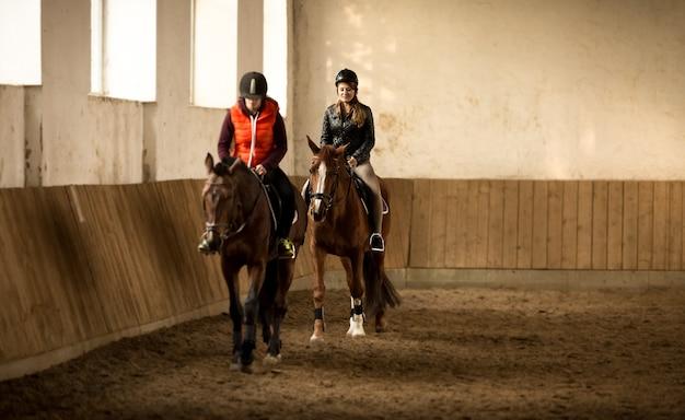 Indoor shot of two woman jockeys doing training in riding hall