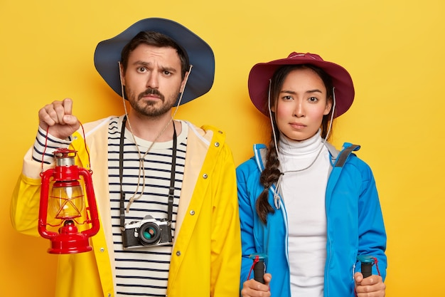Indoor shot of unhappy mixed race woman and man stand next to each other, use kerosene lamp for lightening, trekking poles, isolated on yellow