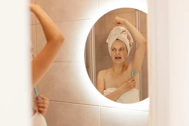 Indoor shot of unhappy woman shaving armpit in bathroom with razor, looking at her mirror reflection with negative facial expression, hygiene procedures at home.