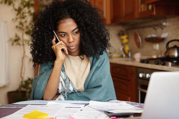 Tiro al coperto di infelice giovane donna con i capelli ricci avente una seria conversazione telefonica