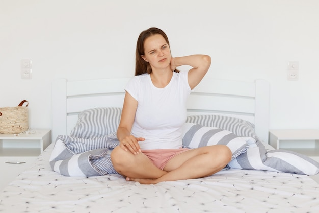 Indoor shot of unhealthy woman with dark hair wearing white casual style t shirt and shorts, sitting on bed in light bedroom with crossed legs, touching painful neck after uncomfortable sleep.