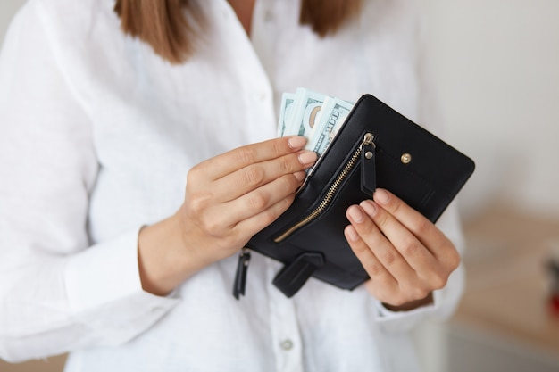 Indoor shot of unknown female wearing white casual style shirt holding black leather wallet with banknotes, saving money.