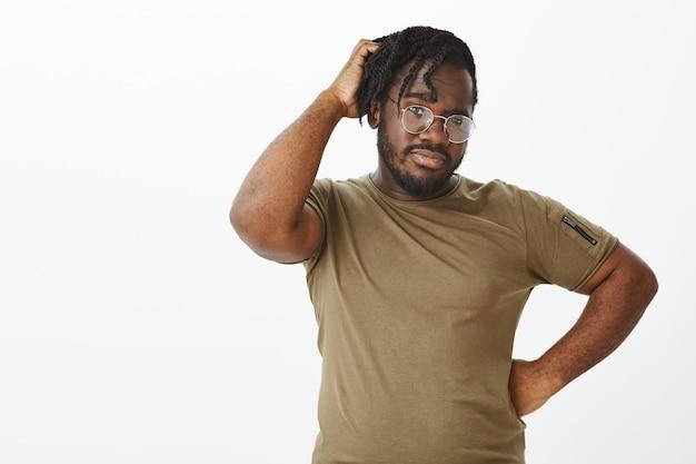 Tiro al coperto di un ragazzo insicuro con gli occhiali in posa contro il muro bianco