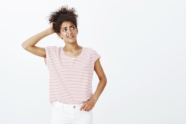 Indoor shot of unsure woman with afro hairstyle posing in the studio