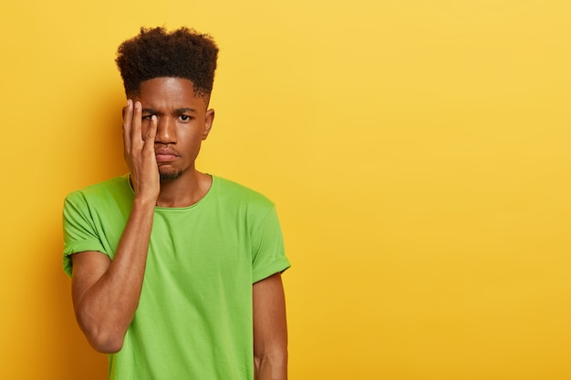 Indoor shot of upset dark skinned man with afro haircut, covers face with palm, has tired facial expression, works long hours preparing for exam, has deadline, wears green t shirt
