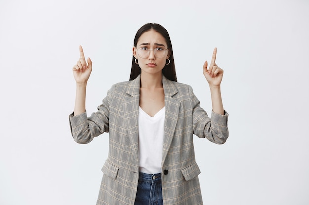 Indoor shot of upset displeased attractive woman in glasses and jacket over t-shirt, sulking and frowning from sadness, pointing up
