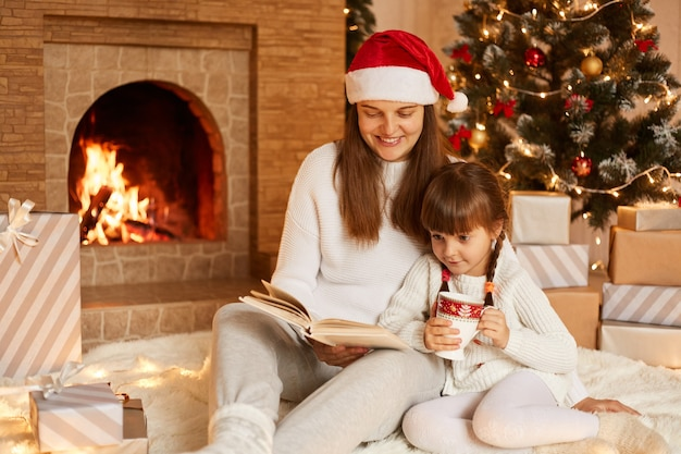 Indoor shot of woman and little girl sitting on floor and reading book, posing in festive decorated living room near fireplace and christmas tree, happy new year.