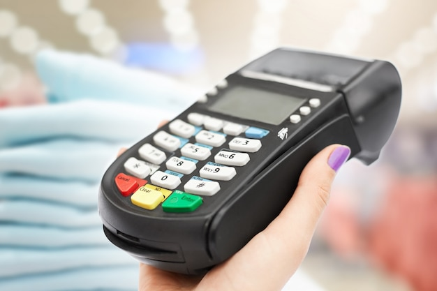 Indoor shot of woman's hand holds pos terminal against boutique interior