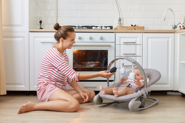 Indoor shot of woman wearing casual striped shirt sitting on the floor in kitchen with her toddler daughter lying in rocking chair, female baking pie or making dinner.