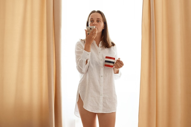 Indoor shot of woman wearing white cotton shirt standing with coffee or tea cup in hands and holding mobile phone, recording voice message, posing against window with beige curtains.