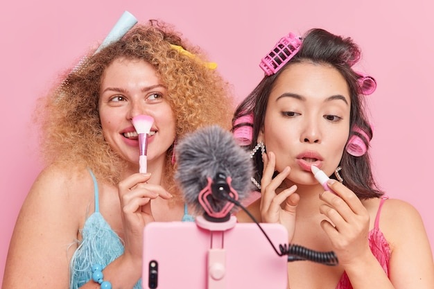 Indoor shot of women bloggers talk about makeup use cosmetic brush apply lipstick give advice to followers how to be beautiful record video via smartphone isolated over pink studio background