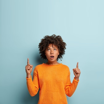Indoor shot of wondered surprised beautiful black woman points upwards, shows direction above, wears orange jumper, isolated over blue wall. impressed dark skinned female promots object