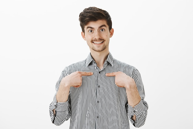 Indoor shot of wondered surprised happy friendly man in striped shirt, pointing with index fingers at chest and smiling broadly, being picked by classmates to represent group in student council
