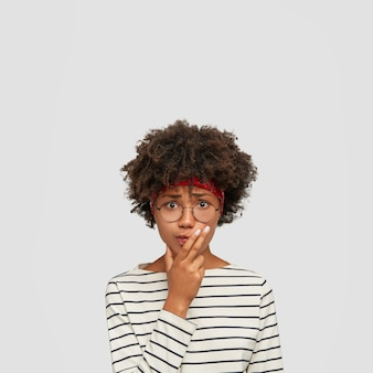 Indoor shot of worried black confused woman keeps hand on chin, looks with puzzled expression