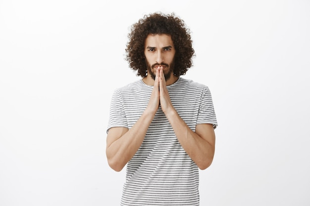 Indoor shot of worried hoping man with beard and curly hair, holding hands in pray over mouth