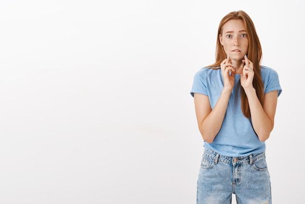 Tiro al coperto di donna rossa di speranza intensa preoccupata con le lentiggini in maglietta blu che si morde il labbro inferiore dal nervosismo incrociando le dita per buona fortuna