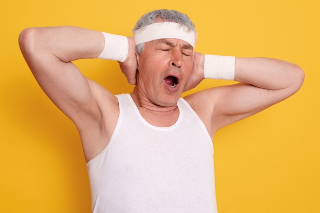 Indoor shot of yawning senior man keeping hands up, keeps mouth opened and eyes closed,  looks sleepy after playing sports
