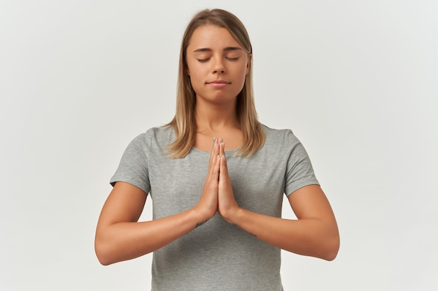 Indoor shot of young adult female keeps her palms together in praying position. meditating, smiling and keeps her eyes closed, isolated over white background