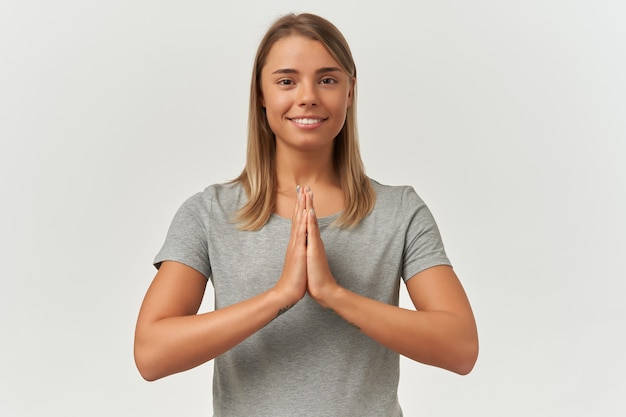 Indoor shot of young adult female keeps her palms together in praying position. meditating, smiling and keeps her eyes opened, isolated over white background