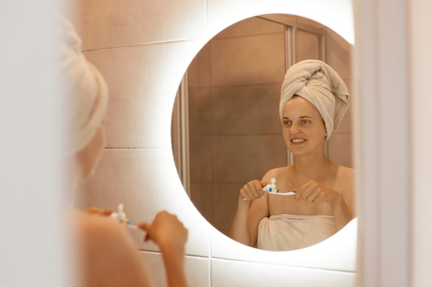 Indoor shot of young adult woman brushing teeth in bathroom, looking at her reflection in the mirror, standing with bare shoulders and white towel on her hair.