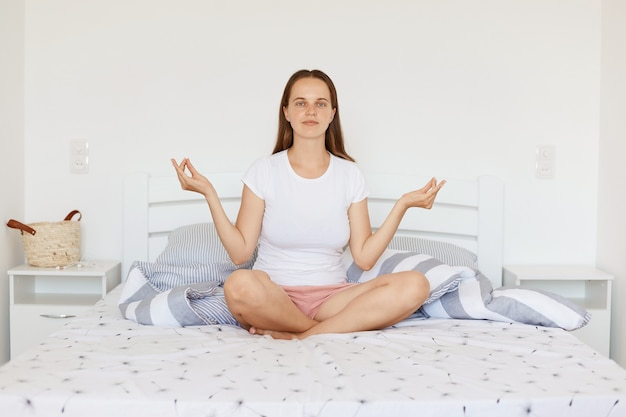 Indoor shot of young adult woman with dark hair wearing white casual style t shirt and shorts, sitting on bed in light bedroom, doing yoga practice and meditating, looking at camera.
