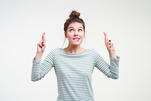 Tiro al coperto di giovane donna castana attraente con acconciatura panino alzando le mani con le dita incrociate e guardando preoccupantemente verso l'alto, isolato sopra il muro bianco