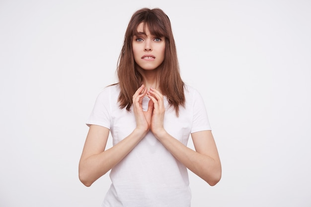 Indoor shot of young attractive dark haired lady with natural makeup keeping folded hands on her chest while looking confusedly , isolated over white wall