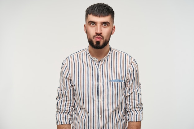Indoor shot of young attractive dark haired man with beard rounding his eyes while looking  with folded lips, keeping his hands along body while posing over white wall
