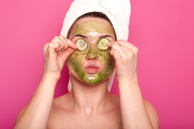 Indoor shot of young attractive woman with green mask on her face putting parts of cucumber on her eyes, protruding her lips, having naked body, wears white towel on her hair, relaxing spa time.