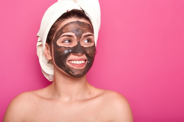 Indoor shot of young attractive woman with white towel on her head, has naked body, smilling isolated on pink in studio, looks aside, having chocolate mask on her face. skincare concept.