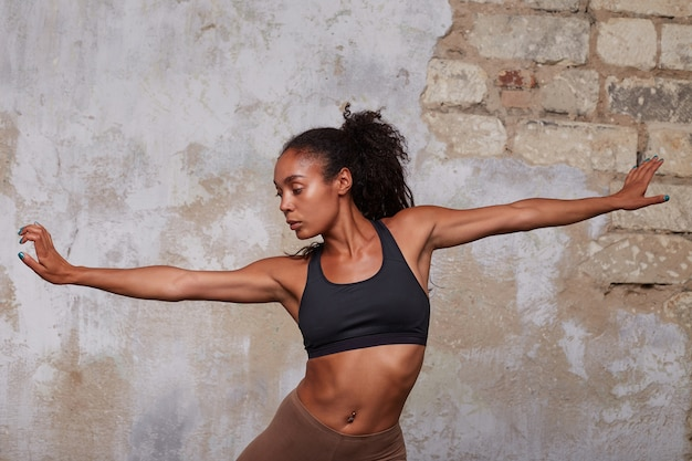 Indoor shot of young beautiful dark skinned curly female with belly button piercing rehearsing modern dance, posing over brick wall with opened arms