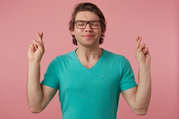 Colpo al coperto di un giovane maschio brunetta, tiene il dito incrociato e prega, indossa una maglietta blu e occhiali