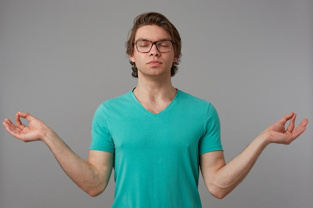Indoor shot of young brunette male, shows mudra sign and praying. isolated over gray background
