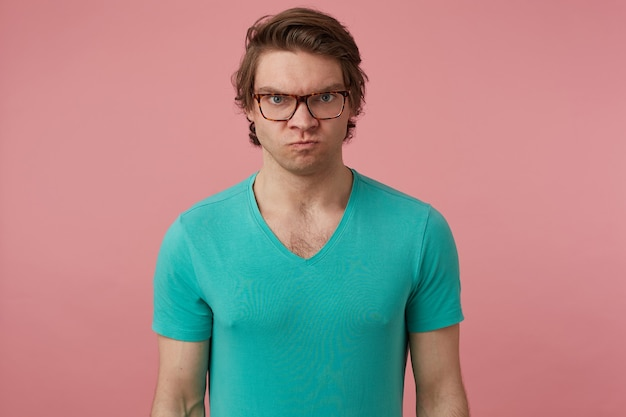 Indoor shot of young brunette man, wears glasses and blue t-shirt, looks directly into camera with mad negative facial expression
