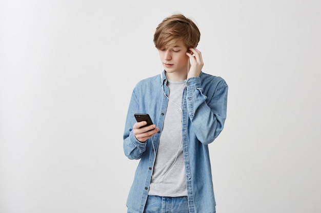 Indoor shot of young caucasian man with fair hair dressed in denim shirt resting after classes at university. guy listening music in white earphones, using music app on smartphone.