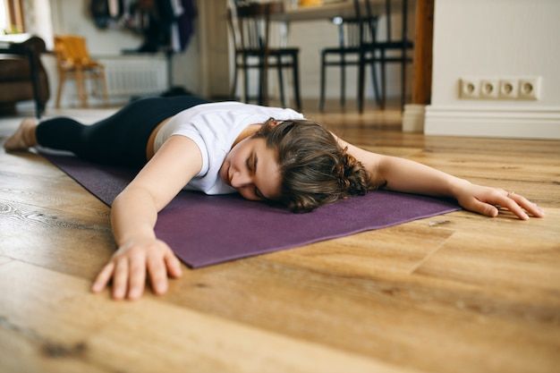 Indoor shot of young caucasian woman in sportswear lying on stomach on mat keeping arms stretched out to front, having rest in calming pose between asanas, doing hatha yoga at home, relaxing body
