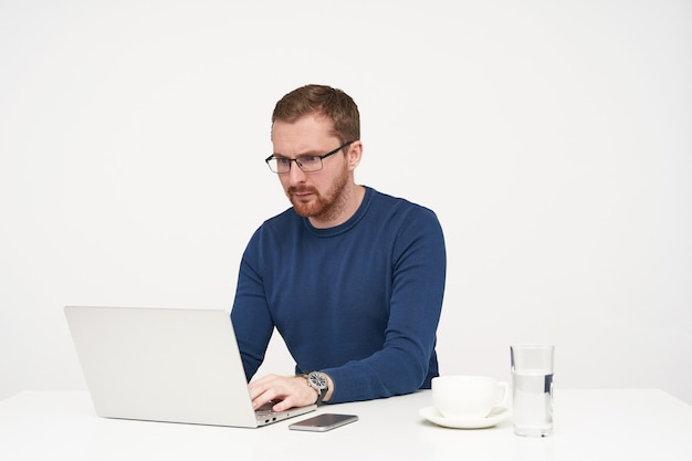 Indoor shot of young concentrated bearded guy in glasses looking seriously on screen of his laptop while working and keeping hands on keyboard, isolated over white background