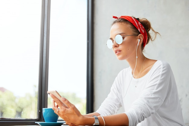 Indoor shot of young cute woman wears red headband and sunglasses, listens favourite composition from playlist via mobile phone, connected to wireless internet and earphones at cozy coffee shop