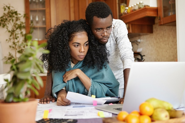 Indoor shot of young dark-skinned couple managing family budget at home