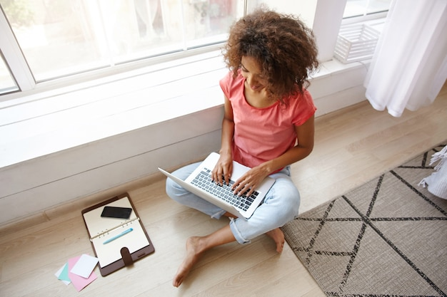 Indoor shot of young dark skinned female with brown curly hair sitting on floor with crossed legs, writing e-mail with her modern laptop, wearing casual clothes