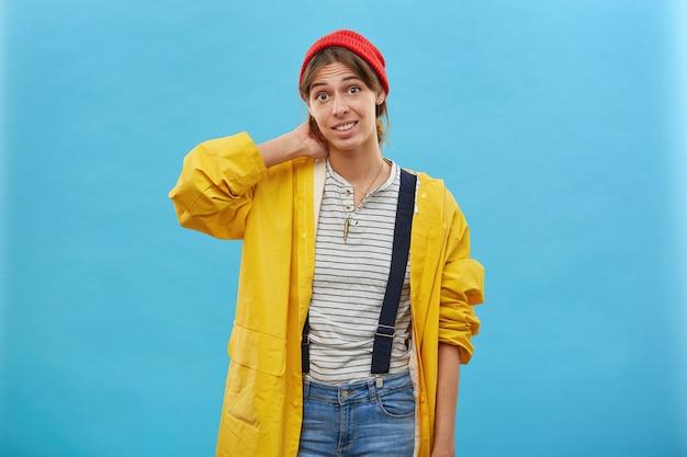 Снимок в помещении: молодая самка в желтой свободной куртке, джинсовом комбинезоне и красной шляпе, держащая руку на шее, собирается прогуляться в лесу за грибами или ягодами. женщина, одетая небрежно на синей стене