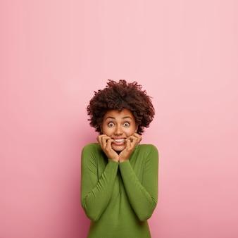 Tiro al coperto di giovane modello femminile morde nervosamente le unghie delle dita, ha gli occhi ben aperti, ha le trecce di qualcosa di orribile nella vita, vestito con un maglione verde, isolato sul muro rosa con lo spazio della copia