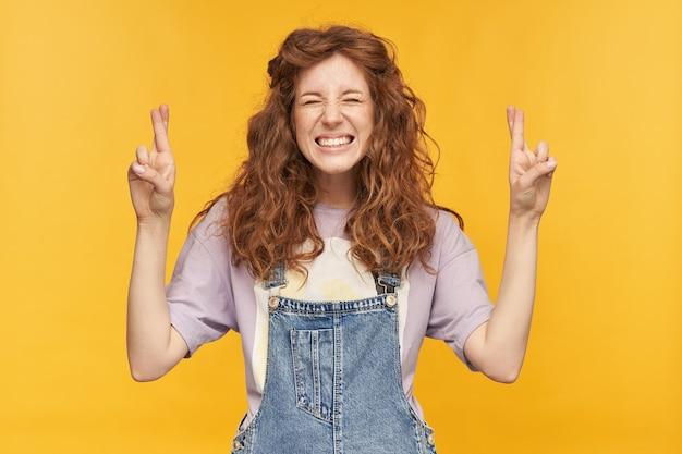 Il tiro al coperto di una giovane studentessa indossa una tuta di jeans blu e una t-shirt viola, incrocia le dita in posizione di preghiera, in attesa di un buon risultato degli esami. isolato su muro giallo
