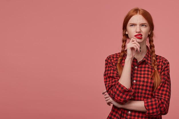 Il tiro al coperto di una giovane donna allo zenzero guarda da parte lo spazio della copia con una smorfia negativa, mordendosi il labbro. isolato su sfondo rosa