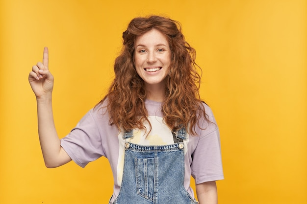 Il tiro al coperto di una giovane donna allo zenzero indossa una tuta di jeans blu e una t-shirt viola, puntando con un dito verso l'alto, sorridendo gioiosamente con un'espressione facciale positiva